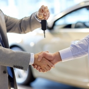 Man handing car keys to another man